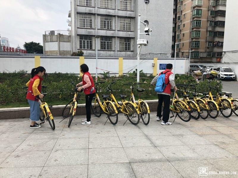 义工和社工在摆放共享自行车.jpg