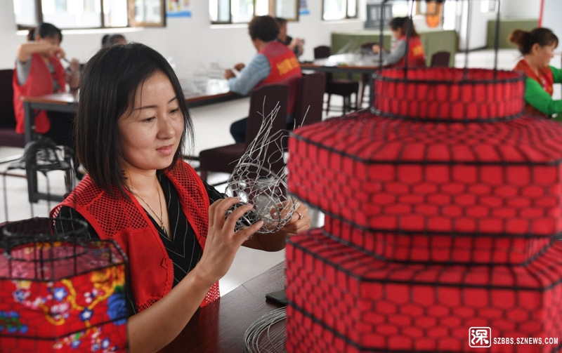 """8月22日,广灵县旭隆工艺品制作有限公司员工在制作仿古灯笼。该公司在6个乡镇设立了""""扶贫车间"""",培训并吸 ..."""