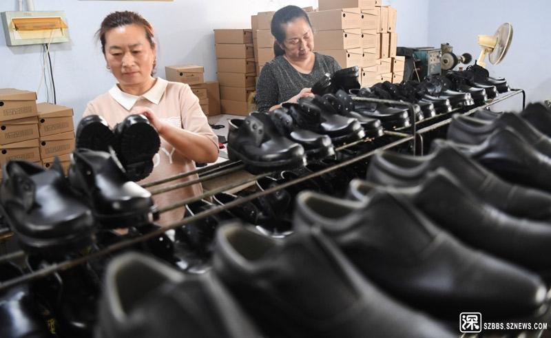 """8月22日,广灵县腾翔鞋服有限公司员工在检验产品,该公司的""""扶贫车间""""吸纳了壶泉镇商村村民就业。 ..."""