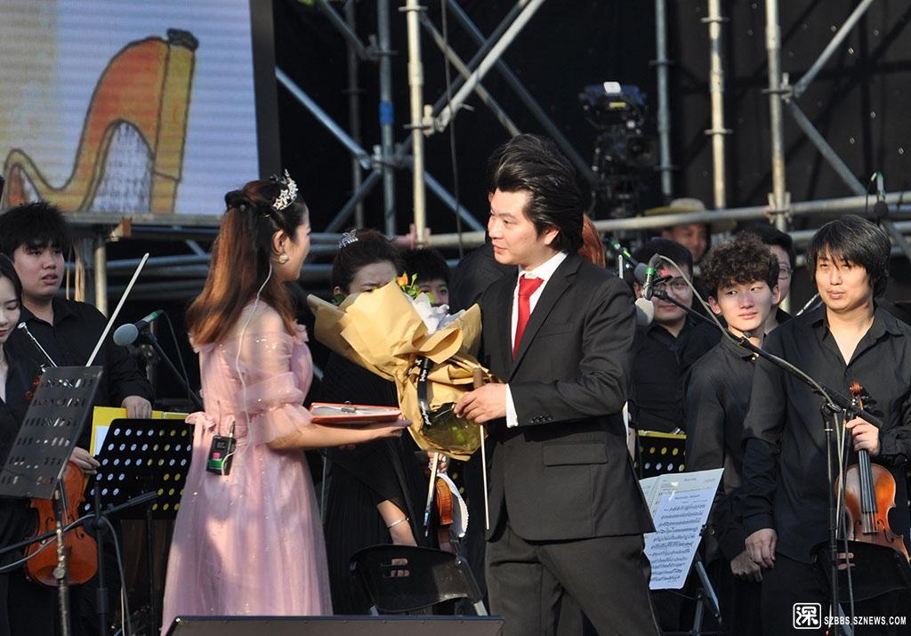 DSC_3120演出结束后指挥家将观众送上来的鲜花转送给朗诵演员.JPG